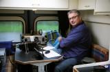"""Joeri PE5JW is zijn radiohoekje aan het inrichten in de eethoek. Zelf zit ik aan mijn """"bureau"""" in de omgedraaide bestuurdersstoel."""