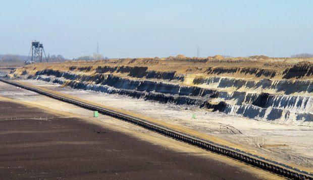De grond wordt laag voor laag afgegraven en afgevoerd door de enorme machine in de verte. Op de volgende foto de machine gezien van de andere kant...