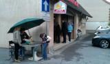 Een rij voor de bakker, een jongetje koopt bloemen vanwege 1 mei.