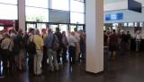 In de rij voor de kassa's. En er tegenover nog zo'n rij kassa's met nóg meer mensen...