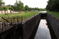 Het oude, in onbruik geraakte schutsluisje in het kanaal d'Orléans. Op de achtergrond de camperplaats.