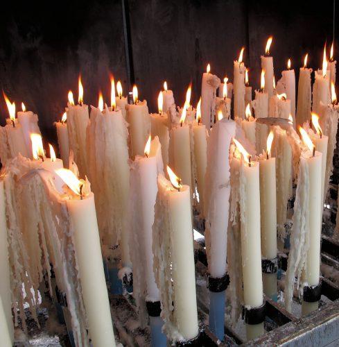 Een lange rij speciale kasten vol met kaarsen.