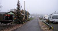 Klaar voor vanavond: kerstboom, grote vuurkorf en op de achtergrond het blokhut-caffeetje van de camperplaats. Wij staan een eindje verder, links van de weg.