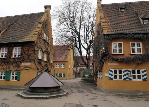 Een doorkijkje in de ommuurde wijk 'Fuggerei', de oudste nog werkende vorm van sociale woningbouw ter wereld.