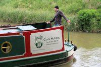 Deze huurder stuurt zijn narrowboat behoedzaam de sluis in.