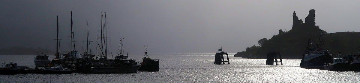 Opkomende zon boven haven en ruïne bij de pier...