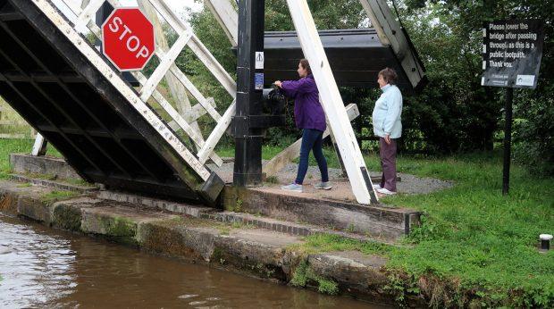 Moeder en dochter doen onderweg een bruggetje open, zodat ...