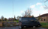 Op de camperplaats in IJlst. Achter het hek onze mast met VHF-vertical en 40m-dipool draadantenne.