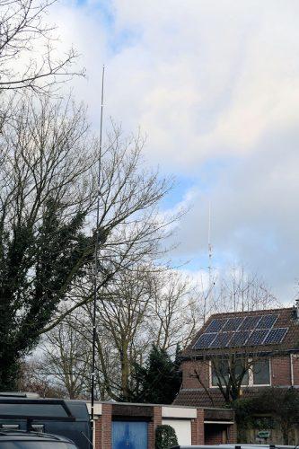 De dualbandantenne met op de achtergrond de antennes aan ons huis.