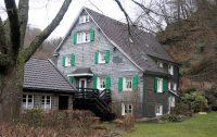 Typisch met leisteen bekleedde woning. Met de voor Brug kenmerkende groene luiken.