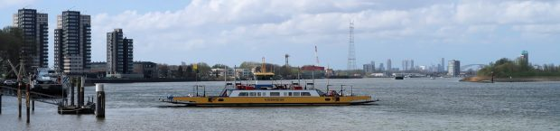 De veerboot bij de molens van Kinderdijk. Op de achtergrond de stad Rotterdam.
