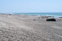 Het strand links, met hier en daar een van het duin gerolde Duitse bunker...