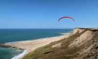 Een prachtig gezicht op zee en de paragliders.