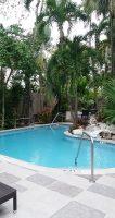 Zwembad en omgeving overdag. Op de achtergrond het terras waar 's ochtends wordt ontbeten.