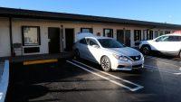 Een motel: kamer op de begane grond, de auto ervoor geparkeerd.