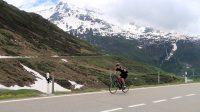 Een vriendelijke fietser zwaait naar de camera.