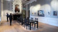 Zaaltje in het kasteel: schilderijen aan de muren, een glazen tafel (kunst, niet aanraken!) in het midden.