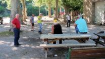 Dorpsbewoners spelen pétanque in de schaduw van de platanen op het dorpsplein.