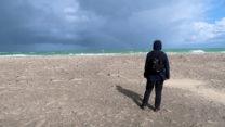 Femma ziet in de verte een regenboog boven zee.